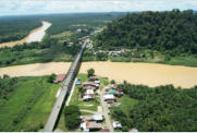The Office of KOPEL Ltd is located under the Kinabatangan River Bridge. In this image is the redish roofed building on the bottom left river-side of the Kinabatangan River Bridge